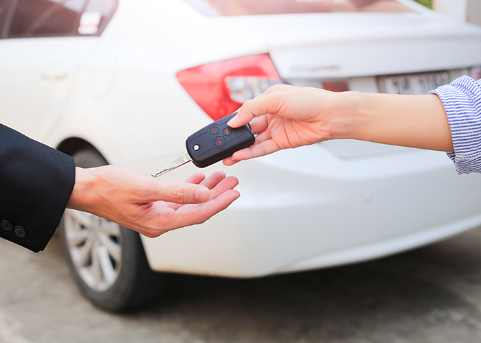 Business hand giving a key for buyer or rental car.